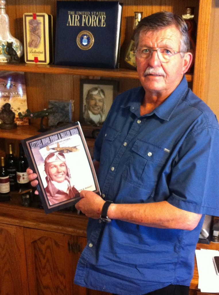 Roger Maraist holding a copy of his book.