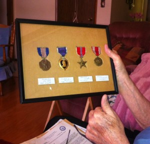 Nyle Smith holding a display of his medals, including the Soldiers Medal (left).