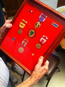 Dave Wall holds the medals he earned while serving with the 24th Infantry Division, including his Purple Heart.