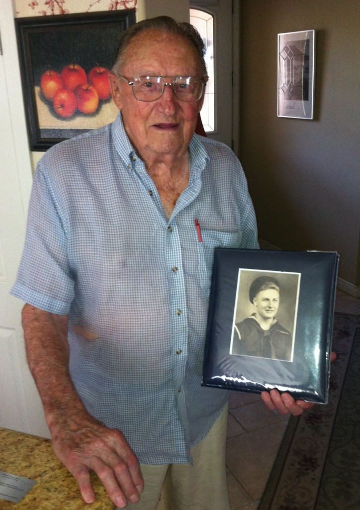94-year-old Willis Shepard holding a photo of himself as a young sailor during WWII.
