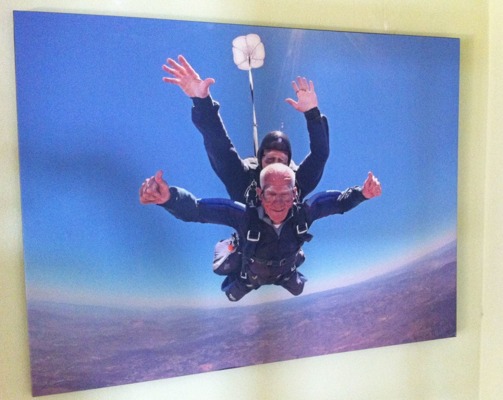 A giant print of a 92-year-old Tom Rice on a tandem skydiving jump on June 6, 2014 adorns the wall of his Coronado home.