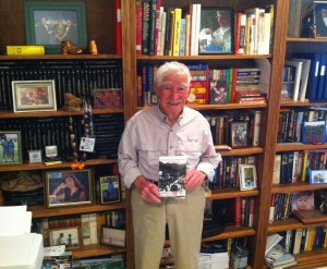 94-year-old Jerry Countess holds the book he wrote, in front of a small fraction of the books he's read.
