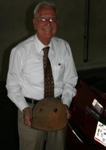 Glenn Schmidt holding his helmet from WWII.