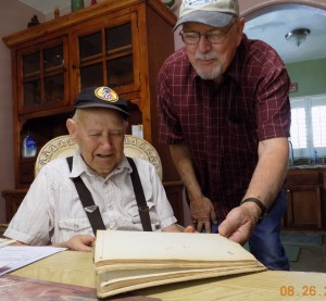 "Orville Lewis and Les Beck look through the ""Wartime Log"" kept by Beck's father in Stalag XVII-B"