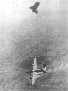 The tiny white dots visible at the bottom of this photo are Irwin and his crewmates escaping their damaged B-24.